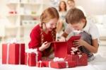 Två barn öppnar julklappar
