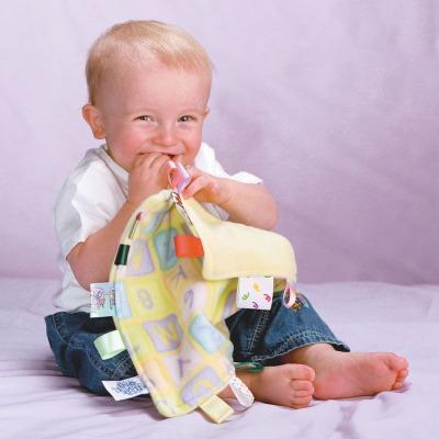 Pojke lekar med en Little Taggies snuttefilt - finns på ABC Leksaker
