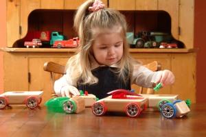 En flicka lekar med Automoblox leksaksbilar i trä - finns på ABC Leksaker